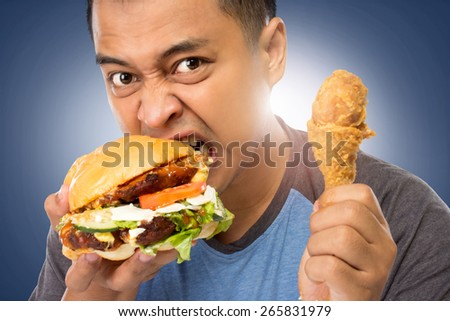 A portrait of a young man bite his big burger deliciously - stock photo