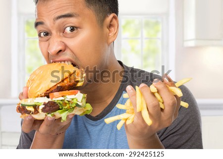 A portrait of a young man bite his big burger deliciously while the other hand holding chips