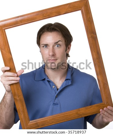 A portrait of a young man holding a frame around his face - stock photo