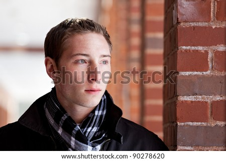 A portrait of a young man standing in an outdoor corridor during winter. - stock photo