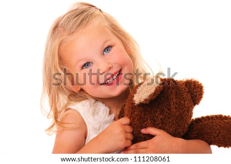 A portrait of a young pretty girl smiling and hugging her teddy bear over white background - stock photo