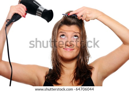 A portrait of a young pretty woman drying and brushing her hair over white background
