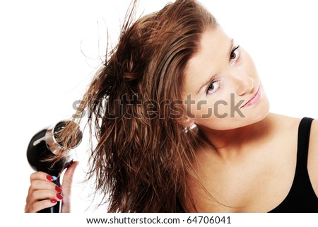 A portrait of a young pretty woman drying her hair over white background