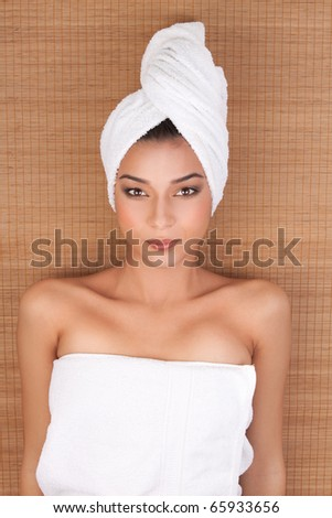 a portrait of a young woman at a day spa, layed on her back, on a mat, with her hair and body wrapped in white towels. - stock photo