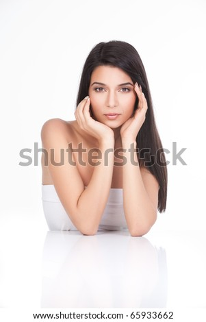 a portrait of a young woman, posing on a white background. she has both her elbows resting on a white table. both her hands are touching her face delicately,
