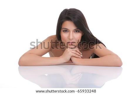 a portrait of a young woman, posing on a white background. she has her arms on a white table and resting her head on her hands. she has a soubtile smile and a relaxed face expression. - stock photo