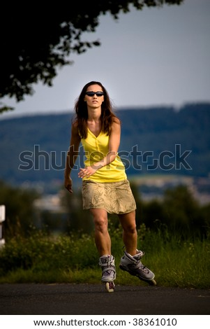 A portrait of a young woman running on the roller skates in the country