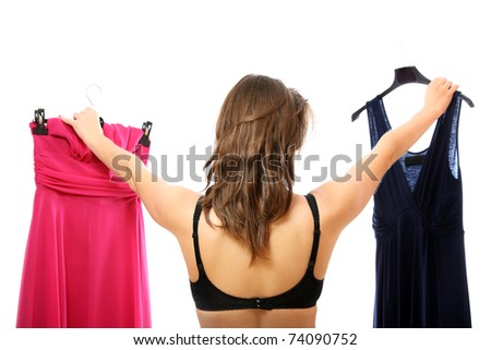 A portrait of a young woman trying to decide between two dresses over white background