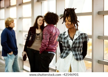 A portrait of an African American woman with dreadlocks with friends in the background