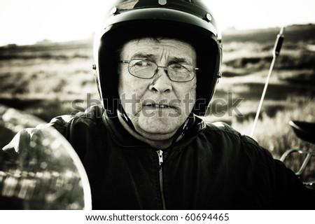 A portrait of an aged man wearing a motorcycle helmet./ Aged Biker - stock photo