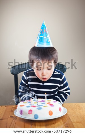 A portrait of an asian boy blowing candles celebrating his birthday - stock photo