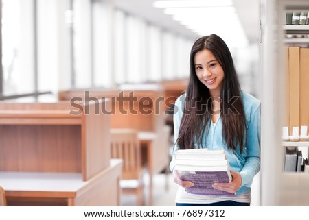 A portrait of an Asian college student holding books in the library - stock photo