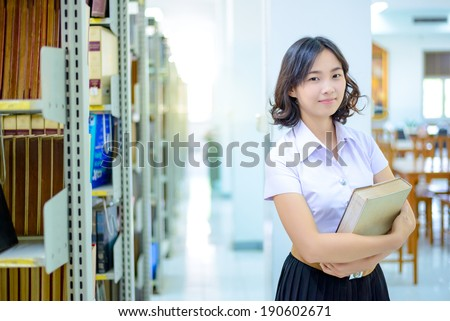 A portrait of an Asian college student in uniform studying in the library , thai student - stock photo