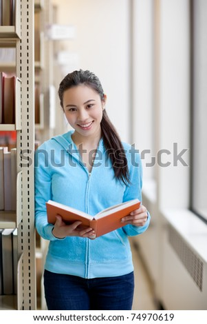 A portrait of an Asian college student studying in the library - stock photo