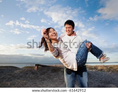 A portrait of an asian couple having fun outdoor - stock photo