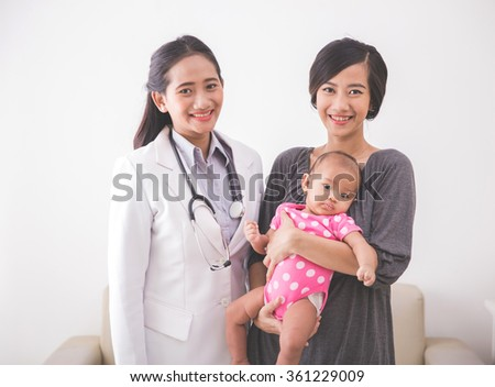 A portrait of an Asian young mother consulting with a pediatrician, holding her baby girl