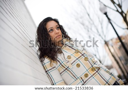 A portrait of an attractive young Indian woman leaning against a white brick wall. - stock photo