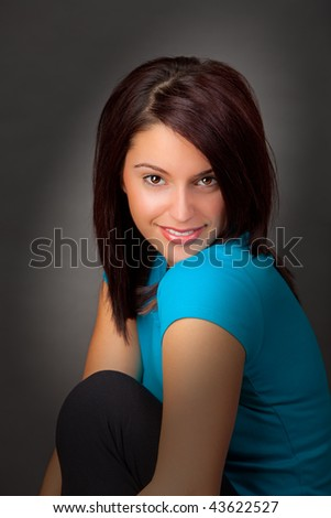 A Portrait of an attractive young woman with spot lighting on her face. - stock photo