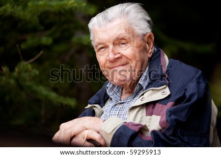 A portrait of an elderly man resting in the forest. - stock photo