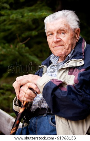 A portrait of an elderly man sitting looking at the camera - stock photo