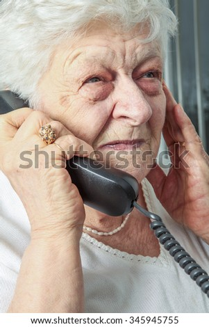 A portrait of an elderly woman on the phone - stock photo