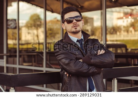 A portrait of an elegantly dressed man in a leather jacket, shirt, tie, jeans, glasses, with a fashionable goatee on the background of the business building. The Life Of The City.