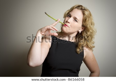 A portrait of an elegantly dressed young, attractive caucasian woman pretending to smoke using an asparagus spear.