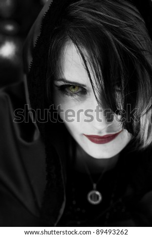 A portrait of an evil possessed vampire woman with red lips and evil eye. - stock photo