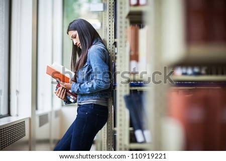 A portrait of an Hispanic college student studying in the library - stock photo
