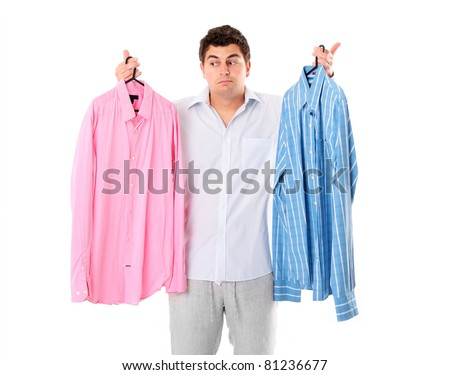 A portrait of an undecided man trying to choose between two shirts over white background - stock photo