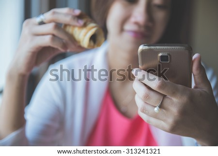A portrait of Asian woman sitting hold a bread while using her handphone in cafe