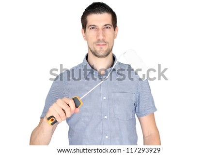A portrait of attractive young man holding a paint brush isolated on a white background