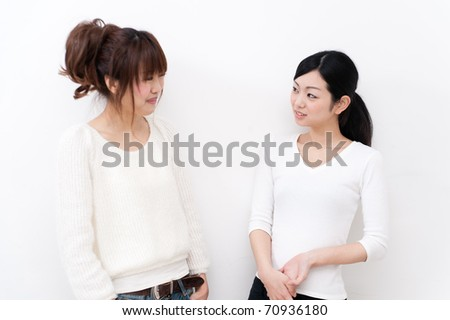 a portrait of beautiful asian sisters talking each other