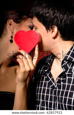 A portrait of beautiful couple with present on valentines - stock photo