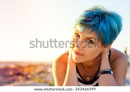 A portrait of beautiful girl with blue hair in sailor's striped top. - stock photo