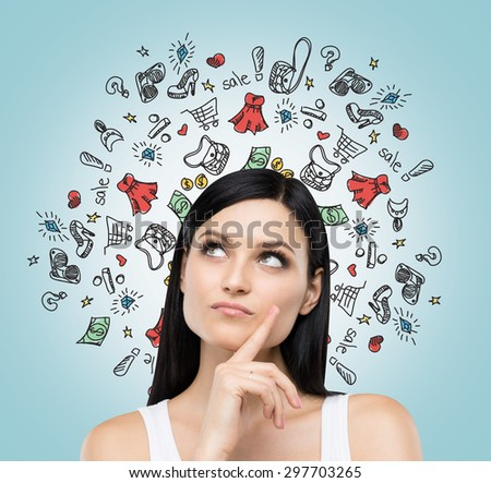 A portrait of beautiful lady who thinks about shopping. Colourful shopping icons are flying in the air. - stock photo
