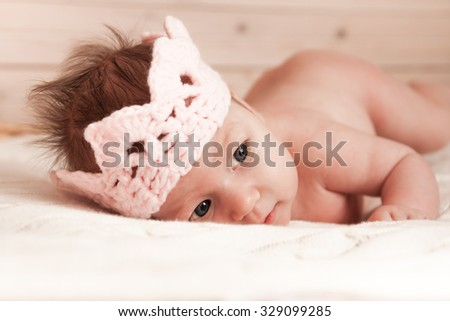 A portrait of cute baby girl with crown on soft blanket  - stock photo