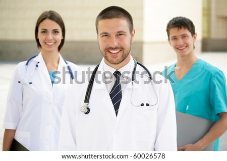 A portrait of doctor with two attractive colleagues in the background - stock photo