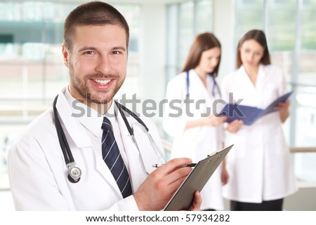 A portrait of doctor with two attractive nurses in the background - stock photo