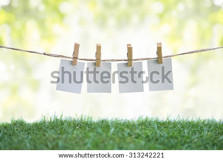 A portrait of Hanging blank paper on clothesline in field. ready for your text - stock photo