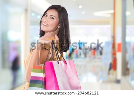 A portrait of happy Asian woman holding shopping bags