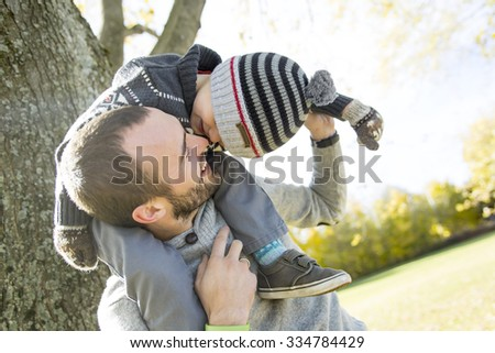 A Portrait of happy father giving son piggyback ride on his shoulders in autumn park. - stock photo