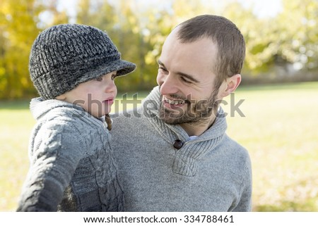 A Portrait of happy father with is son in autumn park. - stock photo