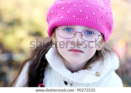 A portrait of little girl in glasses wearing pink cap - stock photo