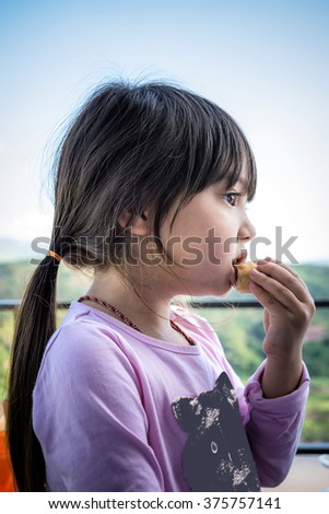 A portrait of long hair pretty little girl eating crispy spring roll with blurry mountain and sky background - stock photo