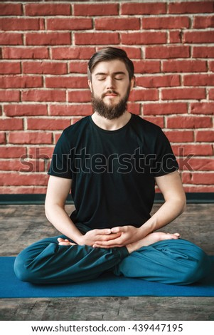 A portrait of man with a beard and closed eyes wearing black T-shirt and blue trousers doing yoga position on blue matt at wall background, copy space, meditating - stock photo
