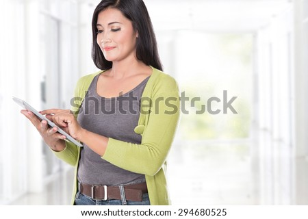 A portrait of middle aged asian woman holding a digital touch screen tablet