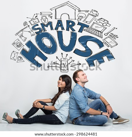 A portrait of Mixed race couple imagining about smart house system, illustrated things - stock photo