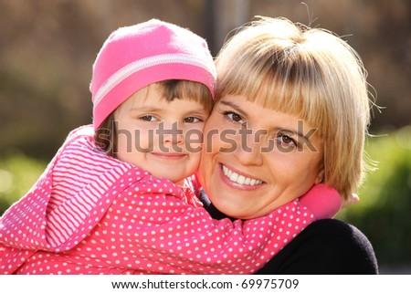 A portrait of  mother and daughter smiling and hugging in the park - stock photo