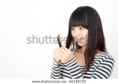 a portrait of pretty asian woman taking care of her hair - stock photo